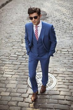 Mens street style fashion: business suit outfit: blue three piece suit with white shirt, brown leather oxford shoes, brown vintage sunglasses, red white candy striped tie