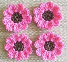 Hilo de algodón Candy Pink 12 flores con centros marrones del ganchillo.  Se trata de un color rosado brillante y hermoso candy. Añadir a páginas de scrapbook, tarjetas, ropa, artesanías, marcos - tan muchas aplicaciones.  Cada flor tiene 9 pétalos redondeados. Son un poco más de 1 pulgada.  Ganchillo en hilo de ganchillo de algodón de tamaño 10.  Hecho a mano por mí en casa libre de humo y mascotas,  Paquete en bolsas de plástico resellables y correo en un envolvente acolchado con…