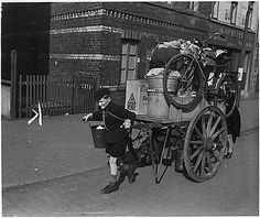 Lad with mother pushing from behind rolls cartload of possessions out of Uerdingen, Germany, moved out by allied military government seeking to prevent loss of life from shelling by Germans on other side of Rhine., 03/19/1945. National Archives.
