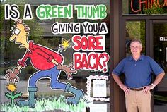 Dr. Kelly Breen stands next to a cartoon painted on his window