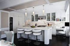 source: GRADE Architecture + Interior Design. Contemporary pendant lighting and white leather bar stools. White cabinetry with slab marble countertops and backsplash. Dark hardwood floor and light paint colors.