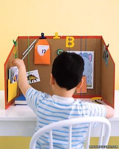 """A studious little one can get down to business in any room -- courtesy of this DIY cubicle. Cut away the bottom, top, and one long side of a large box; trim the height, then slope the sides. Finish edges with colored duct tape. Clamps, rubber bands, and tacks help organize notes, calendars, and other items on the """"walls."""""""