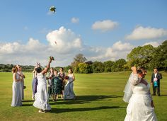 Bride dressed in an wesome white wedding dress throws the flower bouquet to the brides maids