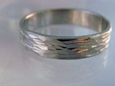 Hammered palladium wedding band is artistic with a dark silver color and a distinctive look.Approximate widths available:4mm wide by 1mm thick5mm wide by 1.5mm thick6mm wide by 2mm thickHammered palladium wedding band is custom-made, made-to-order and takes 2-3 weeks. US quarter sizes 5-12. There is a 25% surcharge for sizes larger than US 12. You may email me your ring size.