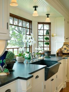 OMG this might be my favorite new white kitchen.. love the black counters and farm sink!