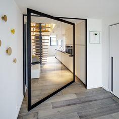 Centraal pivoterende glazen deur met een zwart frame en helder glas. Richtprijs afgebeelde deur +- € 2500.00 excl. BTW.