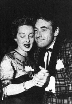 Bette Davis and her husband, Gary Merrill, at a party, 1955.