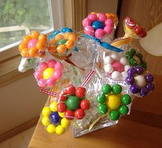 Supplies: (per flower) 1 plastic balloon stick & cups 1 clear elastic band 7 small gumballs 1 large gumball 1 cellophane cut into circle sha...