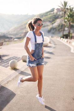 Overol de shorts destruídos con un crop top blanco y un par de tennis casuales para un look deportivo y cómodo. | 18 Looks ideales para las chicas que quieren usar overoles