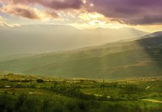 Rural landscape with green hills, mountains and sun rays