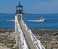 A lobster boat speeds past the Marshall Point Lighthouse on a clear early July day. The light guides maritime traffic at the mouth of the St. George River and Muscongus Bay in the Mid-Coast village of Port Clyde, Maine.