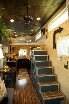 The U-shaped kitchen has a freestanding range, 3/4 refrigerator, butcher block counters, and plenty of storage space with the upper and lower cabinets. A large set of storage stairs provide access to the main loft and a ladder is used to access the guest loft.