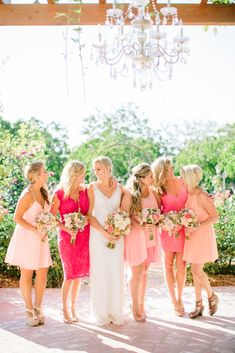 Leading ladies dressed with mismatched dresses in shades of coral and pink