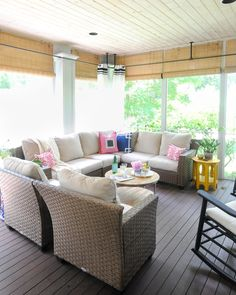 Airy screened porch with neutral furniture, navy blue and pink accents, black and white curtains