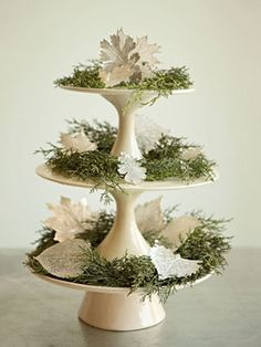 Festive centerpiece idea: Layer cedar and leaves on three cake stands stacked one on top of the other.