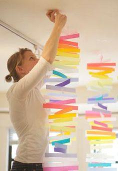 Verschillende stroken gekleurd papier uitknippen en onder elkaar aan een koordje hangen. Een heel mooi effect voor een tuinfeestje!