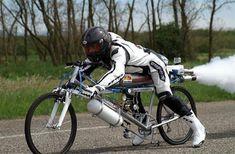Wir sehen hier nicht, wie Francois Gissy in die Pedale tritt, entnehmen den Bildern jedoch, dass er tatsächlich mit einem Fahrrad fährt. Und zwar 263 Stundenkilometer schnell. In Worten Zweihundertdreiundsechzig! Auf einem Raketenrad. Wasserstoffperoxid treibt den nackten Drahtesel ohne Verkleidung so explosiv voran, dass man fürchtet, der Franzose flattere wie ein Fähnchen im Wind. Ein …
