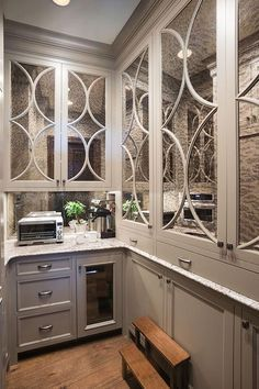 Gray butler's pantry boasts antiqued mirrored eclipse cabinets on top and gray shaker cabinets on bottom paired with a white and gray granite ocuntertops and an antiqued mirrored backsplash.