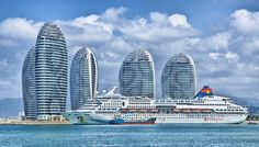 """Off the coast of Hainan Province, a series of Stonehenge-like warped cylinder buildings rises out of Phoenix Island. Part of an artificial archipelago marketed as """"China's Dubai"""", this development was designed by Ma Yansong, a disciple of Zaha Hadid. Riviera Maya, China Shop, Hotel A Dubai, Dubai City, Dubai Uae, Bon Plan Voyage, Dubai Holidays, Cruise Packages, Social Networks"""