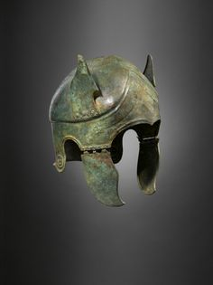 Bronze Samno-Attic helmet  Decorated with unusual sheet bronze wings or ears and a high gabled brow with incised wavy lines to representing hair. Similar helmets have been found in south Italic tombs.