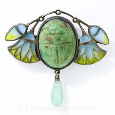 Once the Egyptian tombs were opened in the late 19th century Egyptian revival jewelry became the rage. This lovely brooch is set with a carved green stone scarab beetle (possibly an ancient relic) framed by graceful papyrus flowers and buds crafted of plique-a-jour blue to green transparent glass enamel. Three tiny seed pearls are set in an arch across the top and an aventurine drop is suspended from below.