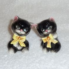 You will love these!! What a darling pair of sweet kitty cats!! These cats are black and are sitting down and have yellow bows around their necks. They