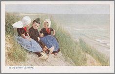 Twee meisjes en een jongen in Walcherse streekdracht, zittend in de duinen bij de zee. De jongen draagt een 'pluumpetje', versierd met een grote veer. na 1905