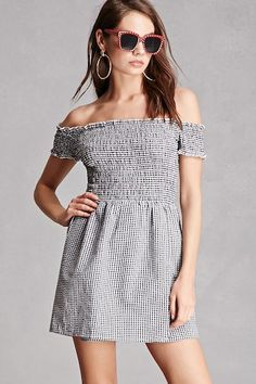 This mini dress by Honey Punch™ features a gingham pattern, smocked bodice with an off-the-shoulder neckline, smocked short sleeves, a crossover hem, and a fit & flare silhouette.