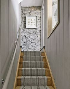 Smarten up a hallway with a tailored stair runner. This narrow staircase has been made super chic framed, as it is, with wood-panelled walls and painted in on-trend pale grey.