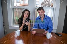 Couple drinking coffee while texting and using a digital PC tablet at the kitchen table | GoMobile Photography