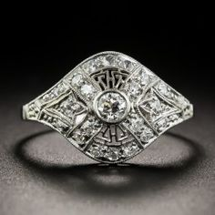 Intricately designed, die-struck and hand-finished in platinum, circa 1925, this consummate Art Deco 'cigar band' style ring sparkles with small bright white European and single-cut diamonds arrayed over a low-profile, finger-hugging dome finished with delicate milgraining. A thoroughly delightful original Jazz Age jewel. The top measures 1/2 inch, currently ring size 7.