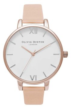A thin bezel rings the creamy clean dial of this elegantly understated round watch balanced on a complementary leather strap.