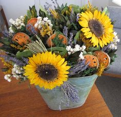 """Fall is here with this delightful and refreshing Mixed Autumn Bouquet Dried Flower Arrangement. Beautifully bunched together in a tin container that measures 17""""Hx15""""Wx8""""D, this creation features English lavender next to natural leaves, preserved natural sunflowers, quince slices, yellow caspia, white ammobium and preserved green myrtle. An arrangement that will catch your eye, no matter where you place it. Please allow 2-3 weeks for delivery, this is one of our Special Order item."""