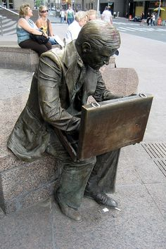 "Double Check, Zuccotti Park, Intersection of Liberty Street and Trinity Place. A bronze 1982 sculpture which was relatively undamaged after 9/11, ""Double Check"" stayed in the park during the recovery effort, and was soon covered with tributes. Returned to the sculptor for repairs, he also created a new cast with all of the tributes attached called ""Makeshift Memorial."" It is in Liberty State Park, NJ, overlooking the WTC site. The repaired ""Double Check"" was returned to its original…"