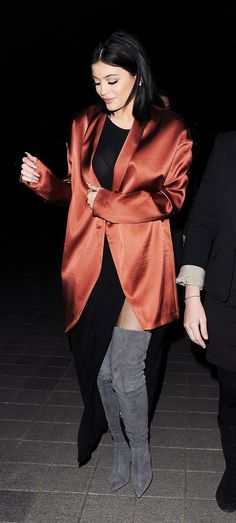 Kylie Jenner wears gray suede over-the-knee boots, a side split black dress, and a burgundy satin blazer.
