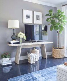 Fall Home Tour modern distressed console table tv gallery wall fig tree in large basket books stacked on floor gray and brass table lamp throws in lidded baskets gray accent wall-2