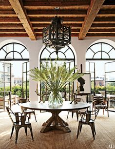 In writer Brad Goldfarb and Ralph Lauren executive Alfredo Paredes's New York City apartment, the living/dining area features a table by Lucca Antiques, a suite of vintage Tolix chairs, and a Spanish wrought-iron lantern from Gustavo Olivieri Architectural Digest, Timber Ceiling, Ceiling Beams, New York City Apartment, Duplex Apartment, Apartment Design, Round Dining, Dining Area, Dining Rooms