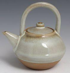"JAPANESE GLAZED STONEWARE TEA POT Japanese stoneware tea pot with celadon glaze. Top portion is glazed while the bottom is left bare. Signed on underside. Size: 6 x 6"""