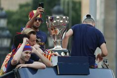 FC Barcelona's Brazilian midfielder Rafinha (top) takes a photo of the Spanish league's cup next to Barcelona's Spanish midfielder Andres Iniesta (L) and Croatian midfielder Ivan Rakitic (2nd L) as they parade on a bus through the streets of Barcelona to celebrate their 24th La Liga title, in Barcelona, on May 15, 2016.Barcelona sealed their 24th La Liga title on May 14, 2016 at Granada to hold off Real Madrid's late-season surge...