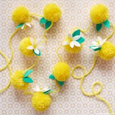 Learn how to make a beautiful lemon garland out of yarn pom poms for a bright piece of home or party decor. This easy project is even safe for kids to craft