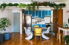 Cozinha integrada com muitas plantas, painel de madeira e armários na cor azul.