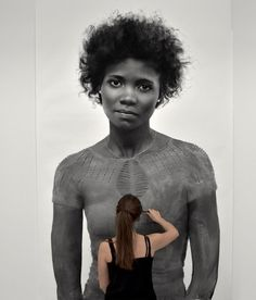 Swiss artist Clio Newton has been hard at work on a series of larger-than-life portraits of women portrayed entirely with compressed charcoal. The towering drawings can reach nearly 8 feet tall and capture near photographic detail of her subject's faces, hair, and bodies. Several of the new portrait