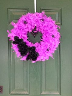 Halloween wreath I made using Dollar Tree materials.  Seven purple feather boas and 2 black rose/spider bouquets.