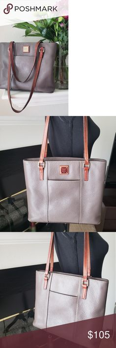 """Dooney & Bourke Small Lexington Bag in Elephant Small Lexington bag. Pebble leather, double straps, metal-plated logo, four bottom feet, top zipper closure, front and back slip pockets. Lined interior, two front-wall slip pockets, one back-wall zip pocket, one back-wall slip pocket, key keeper.Measures approximately 12""""W x 10-1/4""""H x 3-1/2"""" D with an 11"""" strap drop. 100% leather body and trim; 100% cotton lining. Dooney & Bourke Bags Shoulder Bags"""