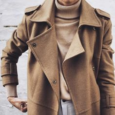 Everything about this classic fall/winter look! Classic camel colored wool trench coat, worn over a camel ribbed polar-neck sweater, with a hint of grey/off-white jeans (fastened with a black button) peeking through. Fall and winter fashion. Minimal   classic layers. Soft, neutral color palette.