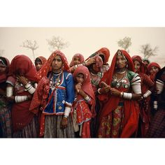 This group of Indian Banjara women live in Rajasthan in the Thar Desert in western India. As a desert storm whips sand through the air, they take shelter beneath their saris and headscarves, and protect themselves from the winds.