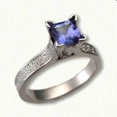 14kt White Gold Celtic Maureen Engagement Ring with the Triangle & Heart knot pattern down shank set with a 1.3ct Princess Cut Blue Sapphire