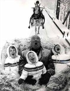 Alfred Hitchcock catching snowflakes during a sleigh ride with his grandchildren 1960