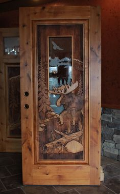Knotty alder door with moose carving & custom etched glass unit