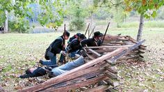 Volunteers, many from the Tenth Michigan Infantry, reenact a Civil War battle Saturday afternoon in Deerfield Park as part of an annual event.